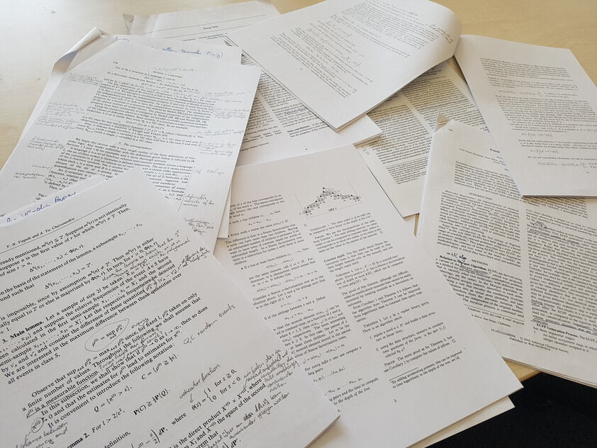 unsorted scientific papers on a desk